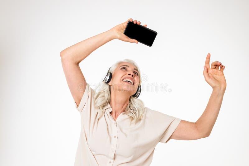 Portret van een blije rijpe vrouw die aan muziek luisteren royalty-vrije stock afbeelding