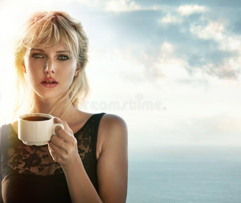 Portret van een blonde het drinken koffie in openlucht stock foto