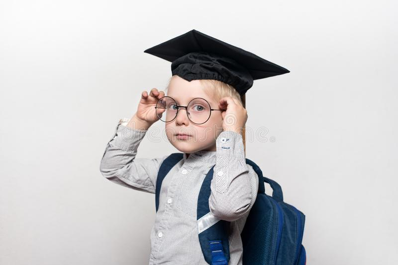 Portret van een blonde jongen in een academische hoed en een schooltas Verbetert glazen Witte achtergrond Het concept van de scho royalty-vrije stock foto's