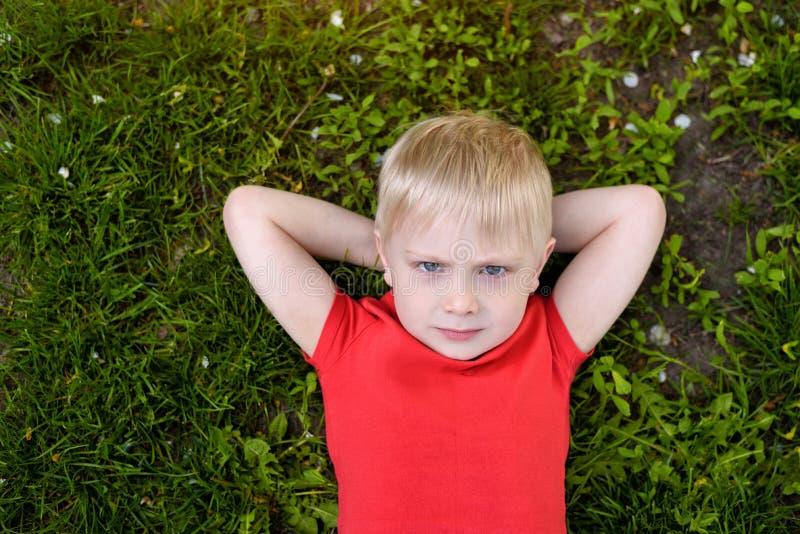 Portret van een blonde jongen die op het gras liggen Handen achter hoofd Rust bij aard stock fotografie