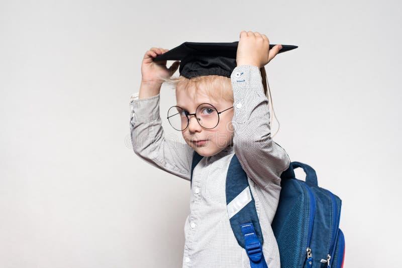 Portret van een blonde jongen in glazen, een academische hoed en een schooltas op een witte achtergrond Het concept van de school stock afbeelding