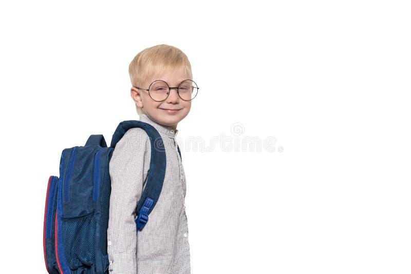 Portret van een blonde jongen in glazen en met een schoolrugzak Het concept van de school isoleer stock afbeelding