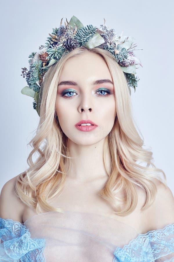 Portret van een blondevrouw met een kroon op haar hoofd en een blauwe gevoelige lichte transparante kleding Grote blauwe ogen en  royalty-vrije stock afbeelding
