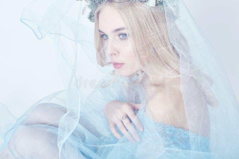 Portret van een blondevrouw met een kroon op haar hoofd en een blauwe gevoelige lichte transparante kleding Grote blauwe ogen en  royalty-vrije stock foto's