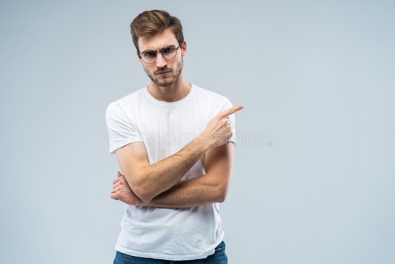 Portret van een boze jonge mens die vingers richten weg op exemplaarruimte op zijn die palm over grijze achtergrond wordt geïsole stock fotografie