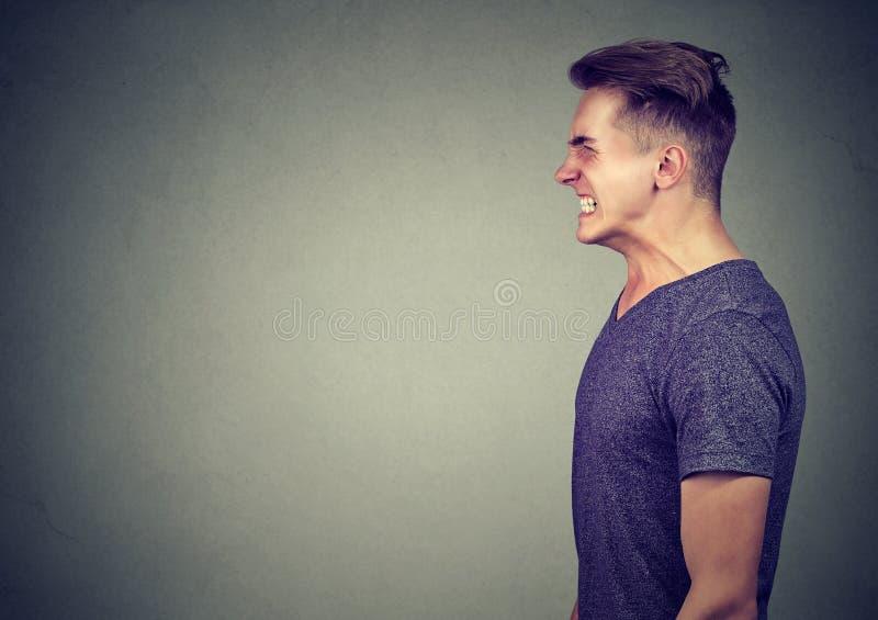Portret van een boze mens die zijn tanden dichtklemmen die tegen verleiding verzetten zich te gillen royalty-vrije stock fotografie