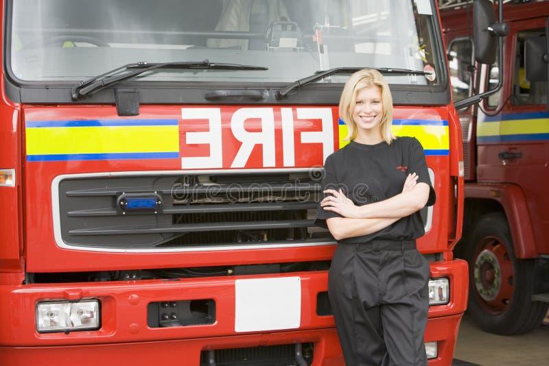 Portret van een brandbestrijder die zich door een motor bevindt royalty-vrije stock fotografie