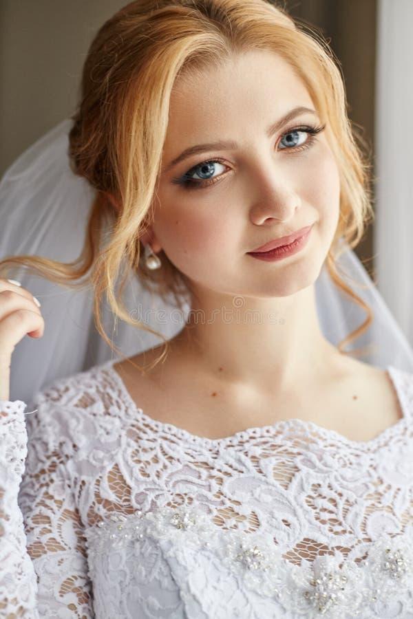 Portret van een bruid in een elegante witte huwelijkskleding die voorbereidingen treffen voor royalty-vrije stock foto's