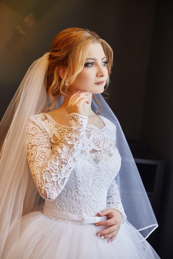 Portret van een bruid in een elegante witte huwelijkskleding die voorbereidingen treffen voor stock foto