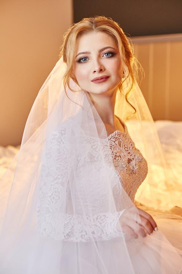 Portret van een bruidzitting in een elegante witte huwelijkskleding op het bed en het voorbereidingen treffen voor de huwelijksce royalty-vrije stock foto's