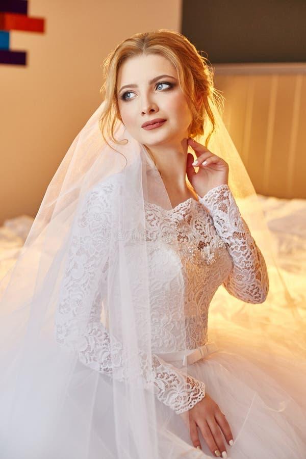 Portret van een bruidzitting in een elegante witte huwelijkskleding op het bed en het voorbereidingen treffen voor de huwelijksce royalty-vrije stock afbeeldingen