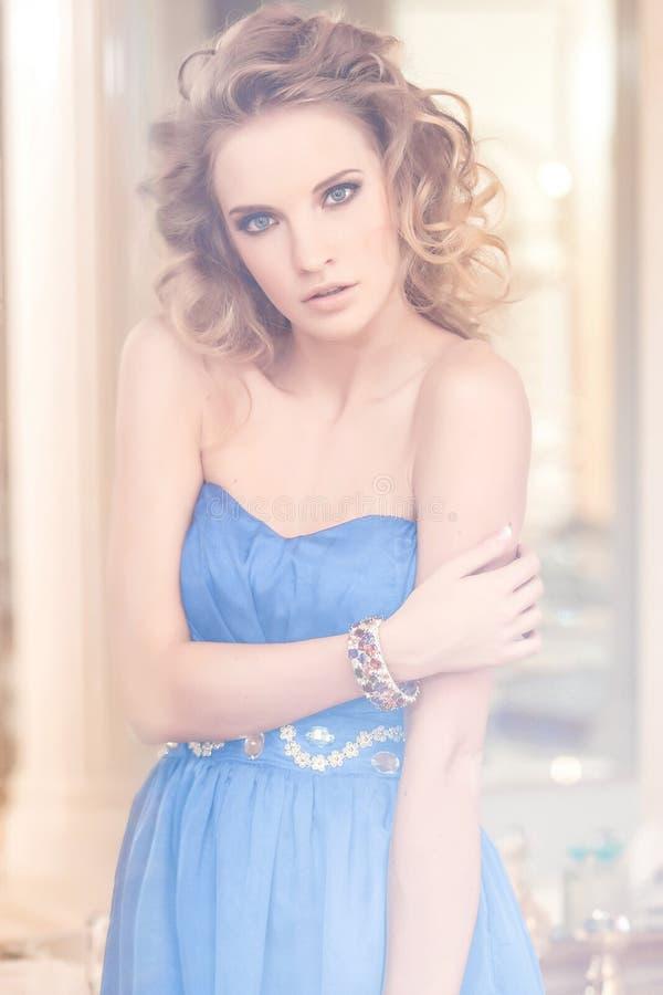 Portret van een charmante vrouw met modieus krullend kapsel die het blauwe kleding stellen naast een spiegel dragen Schoonheid, m royalty-vrije stock foto's