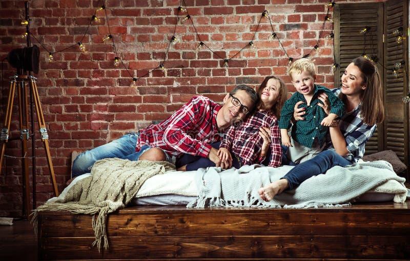 Portret van een cheerrful familie die in modieuze binnenlands ontspannen royalty-vrije stock afbeelding