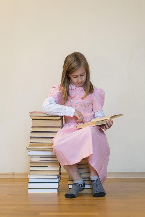 Portret van een de lezingsboek van de meisjestiener Onderwijs en schoolconcept Het kind leest Een weinig leuk meisje in een roze  stock foto's