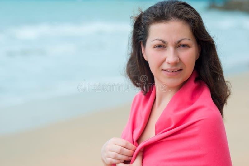 Portret van een donkerbruine die vrouw in een handdoek wordt verpakt stock afbeelding