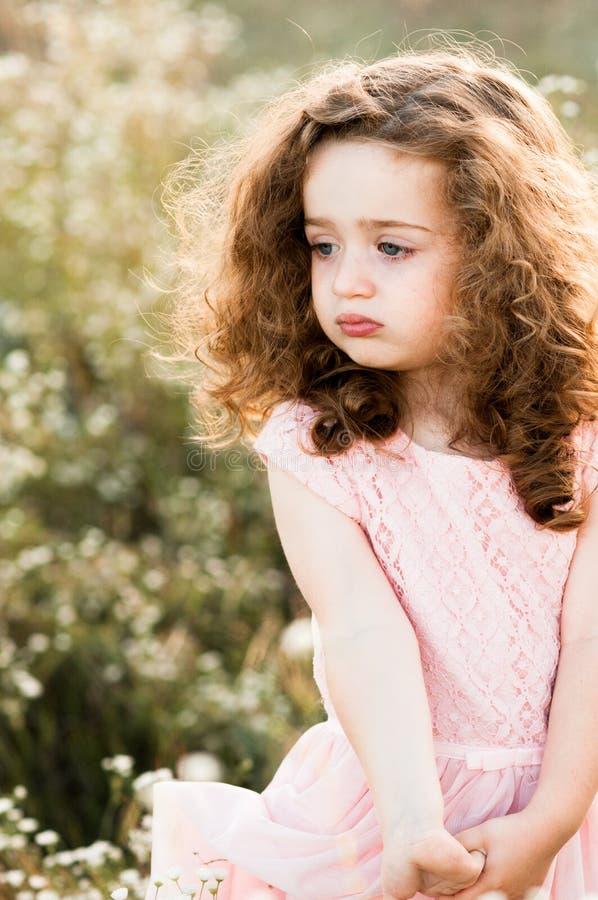Portret van een droevig klein krullend meisje in een roze lange kleding stock foto's