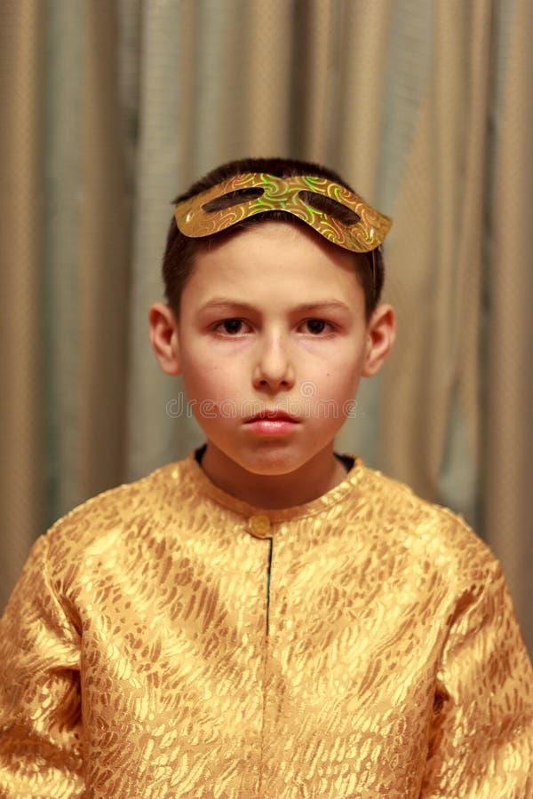 Portret van een droevige jongen in een gouden luim dresst stock afbeelding