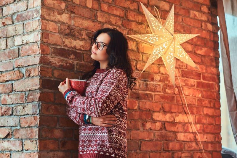 Portret van een eenzaam donkerbruin meisje die oogglazen en warme sweater dragen die een kop van koffie houden terwijl het leunen royalty-vrije stock afbeelding