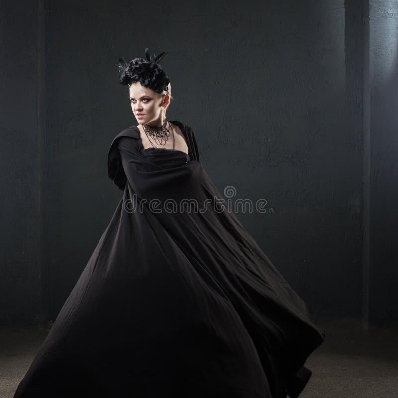 Portret van een elegante Gotische blondevrouw Meisje in kroon van zwarte bloemen en zwarte mantel royalty-vrije stock foto's