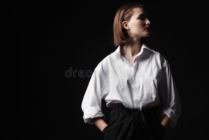 Portret van een elegante jonge vrouw in een wit overhemd en een zwarte broek Interessant studiolicht royalty-vrije stock foto's