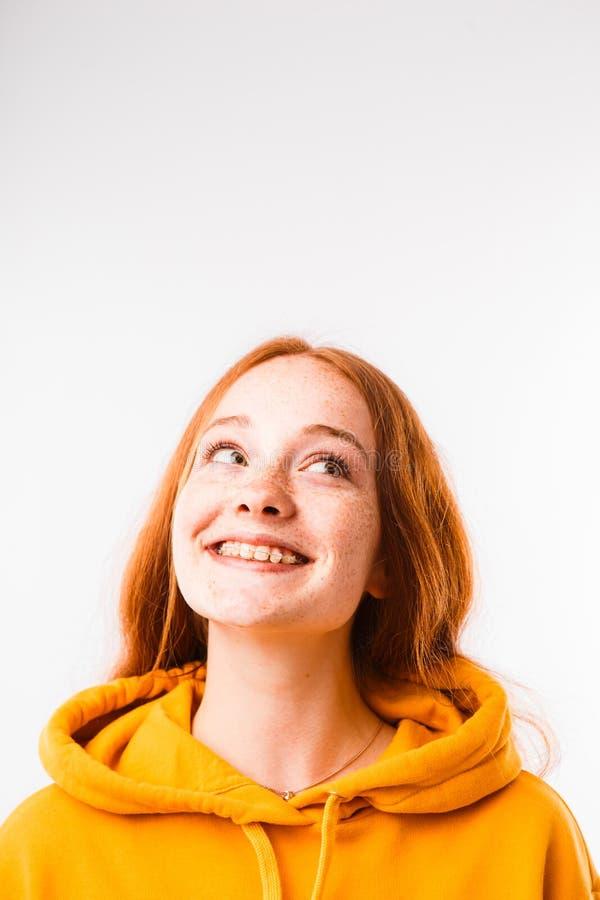 Portret van een emotioneel roodharig meisje met sproeten en steunen op een witte achtergrond royalty-vrije stock foto's