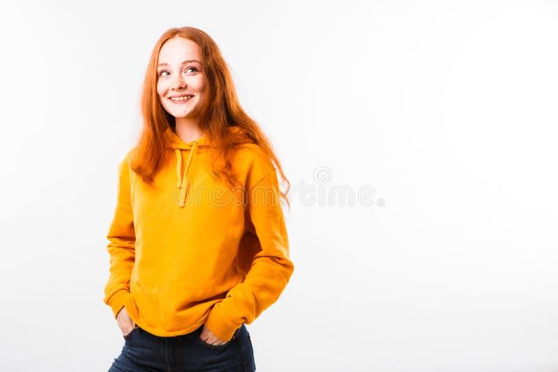 Portret van een emotioneel roodharig meisje met sproeten en steunen op een witte achtergrond stock afbeelding