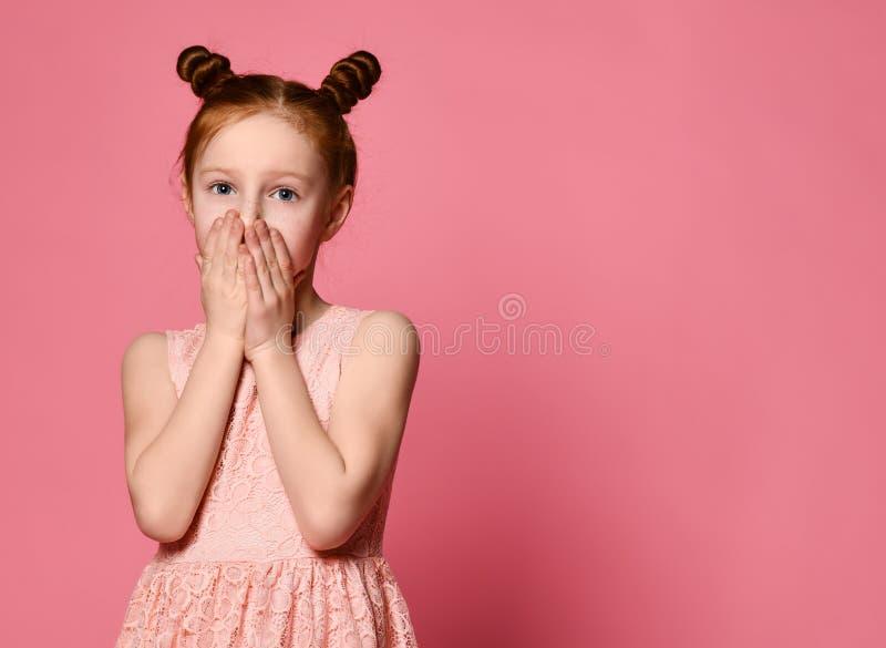 Portret van een ernstig jong gembermeisje die mond behandelen met beide handen die geheim houden stock fotografie