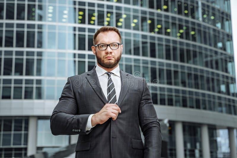 Portret van een ernstige bedrijfsmens in een kostuum en glazen op de achtergrond van een bureaugebouw stock fotografie