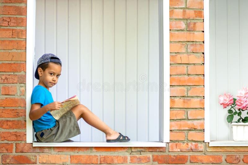 Portret van een ernstige kleine jongenszitting op de veranda dichtbij het oude dorpshuis Het concept ontwikkeling van kinderen royalty-vrije stock afbeelding