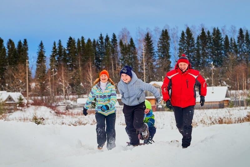 Portret van een familie met vier mensen die pret in de sneeuw hebben royalty-vrije stock afbeelding