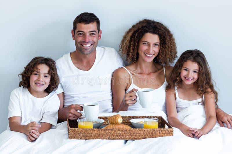 Portret van een familiezitting met ontbijtdienblad in bed stock afbeeldingen