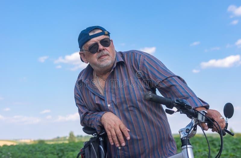 Portret van een gebaarde, mollige hogere mens die klaar aan de zomerrit op een fiets worden stock fotografie