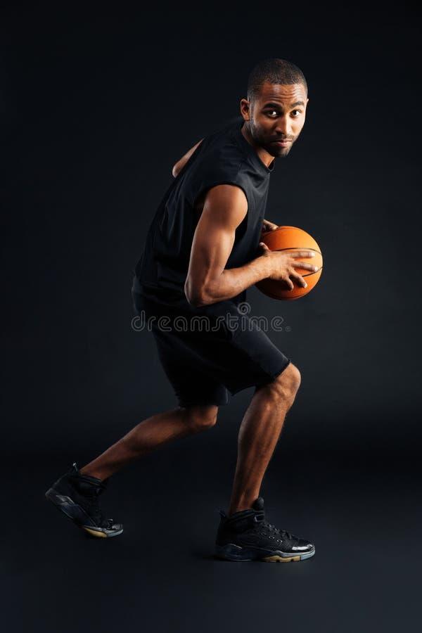Portret van een geconcentreerde Afrikaanse sportenmens die in basketbal speelt stock fotografie
