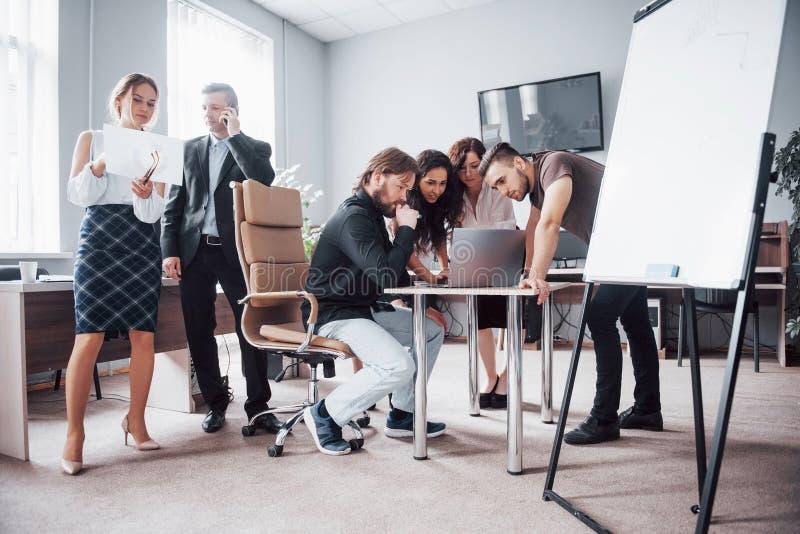 Portret van een gelukkig creatief team van mensen die in het bureau op de vergadering spreken royalty-vrije stock foto's