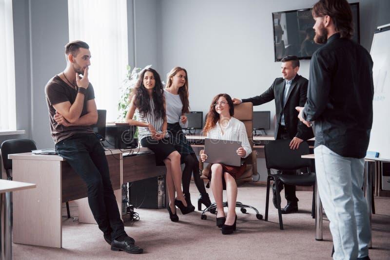 Portret van een gelukkig creatief team van mensen die in het bureau op de vergadering spreken stock foto