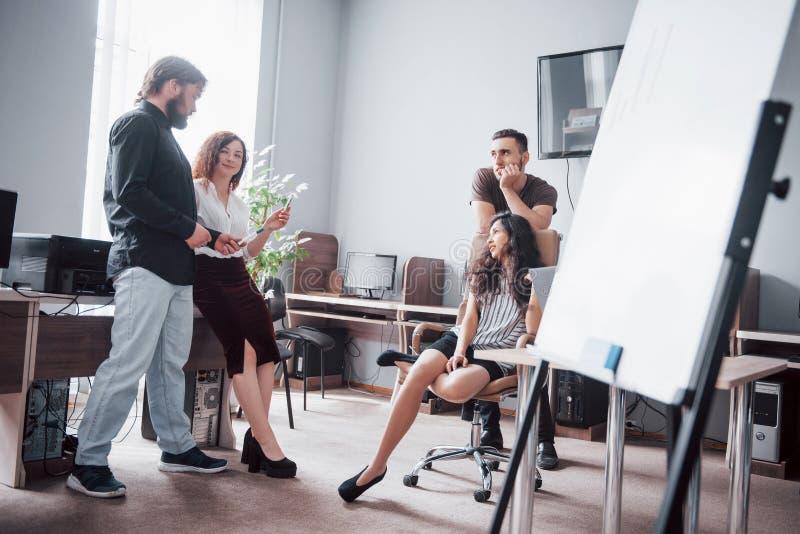 Portret van een gelukkig creatief team van mensen die in het bureau op de vergadering spreken stock afbeelding