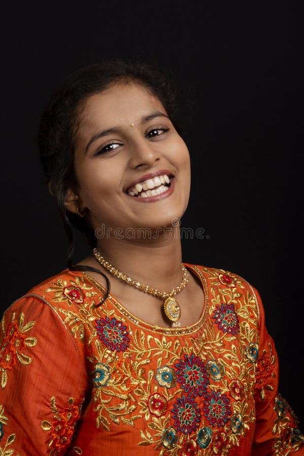 Portret van een gelukkig jong Indisch meisje die op zwarte achtergrond glimlachen royalty-vrije stock afbeelding