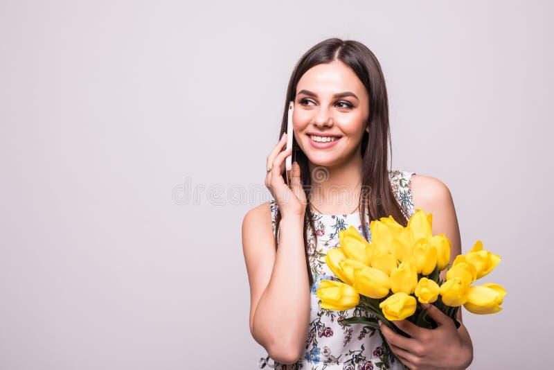 Portret van een gelukkig jong meisje in kleding die op mobiele telefoon spreken terwijl het houden van groot boeket van gele tulp stock foto's