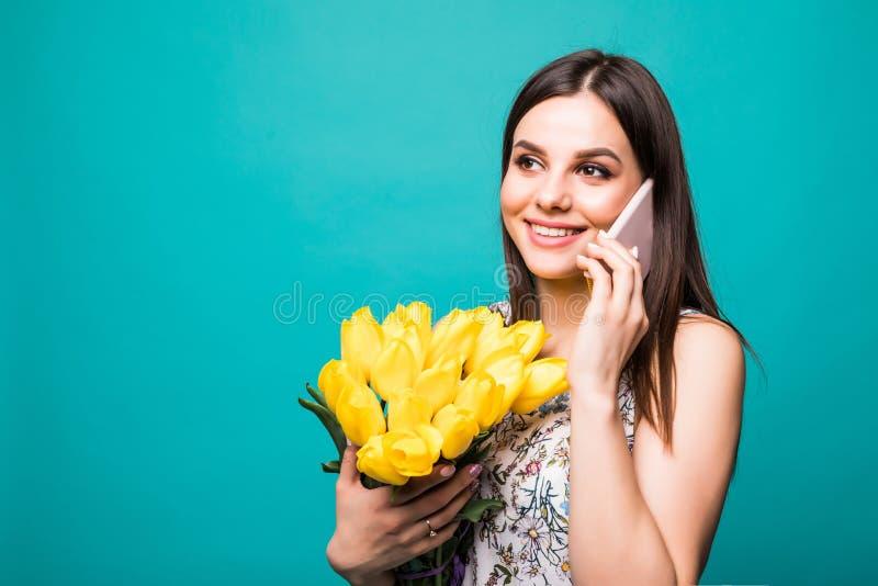Portret van een gelukkig jong meisje in kleding die op mobiele telefoon spreken terwijl het houden van groot boeket van gele die  royalty-vrije stock foto