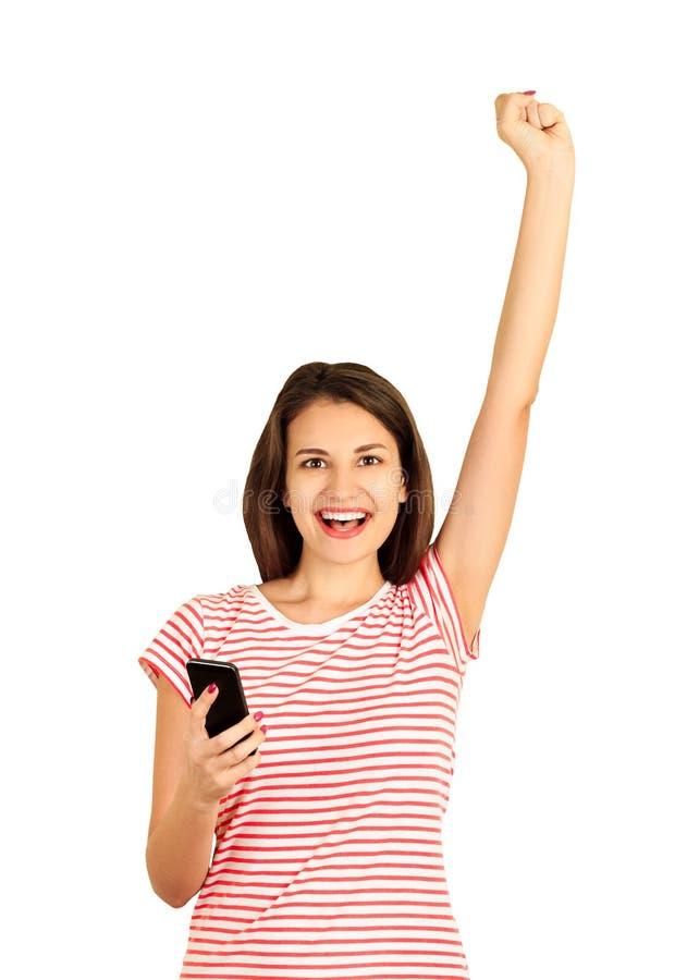 Portret van een gelukkig meisje die een mobiele telefoon houden en haar hand opheffen tot de bovenkant die goed nieuws vieren emo royalty-vrije stock fotografie