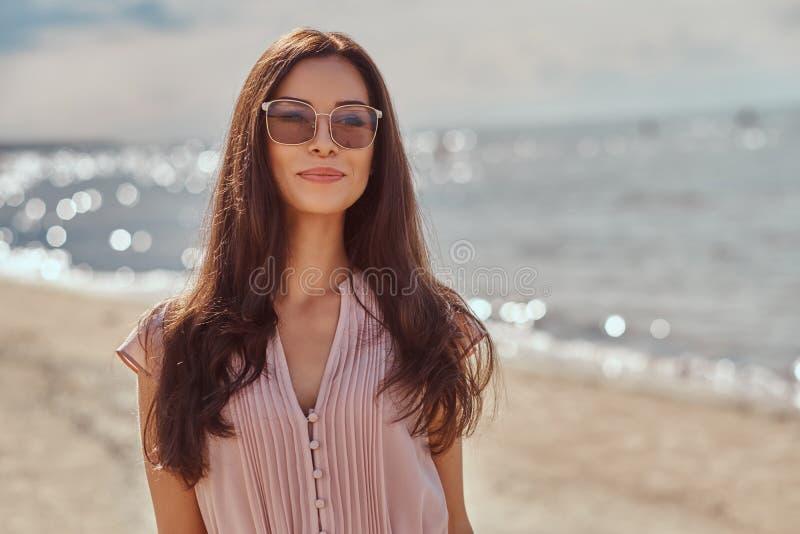 Portret van een gelukkig mooi donkerbruin meisje met lang haar in zonnebril en kleding op het strand royalty-vrije stock fotografie