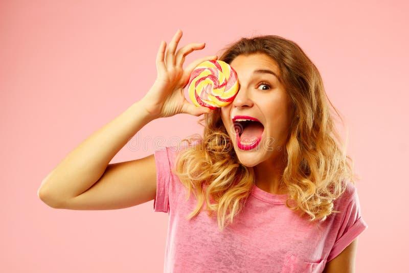 Portret van een gelukkig mooi meisje die zoet suikergoed over roze bedelaars houden royalty-vrije stock foto's