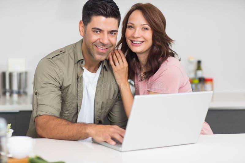 Portret van een gelukkig paar die laptop in keuken met behulp van royalty-vrije stock foto's