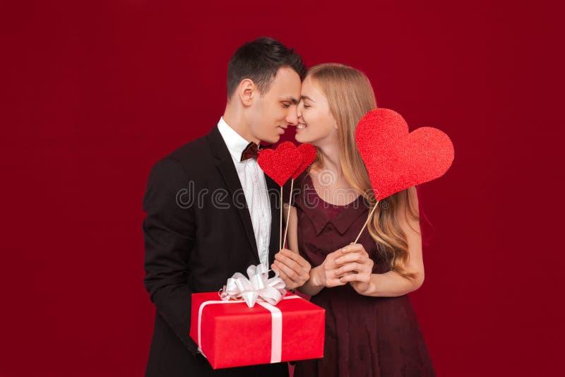 Portret van een gelukkig paar, het document van de mensenholding harten, op rode achtergrond, het concept van de minnaarsdag stock afbeelding