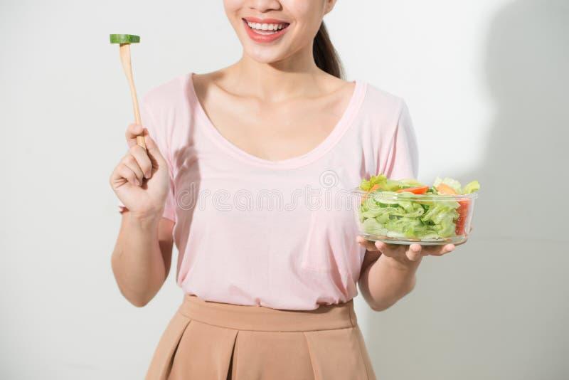Portret van een gelukkig speels meisje die verse salade van een kom eten royalty-vrije stock fotografie