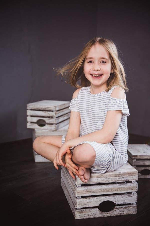 Portret van een gelukkig tienermeisje in de zomerkleding in studio Zij zit op de dozen, de wind die haar haar blazen royalty-vrije stock fotografie