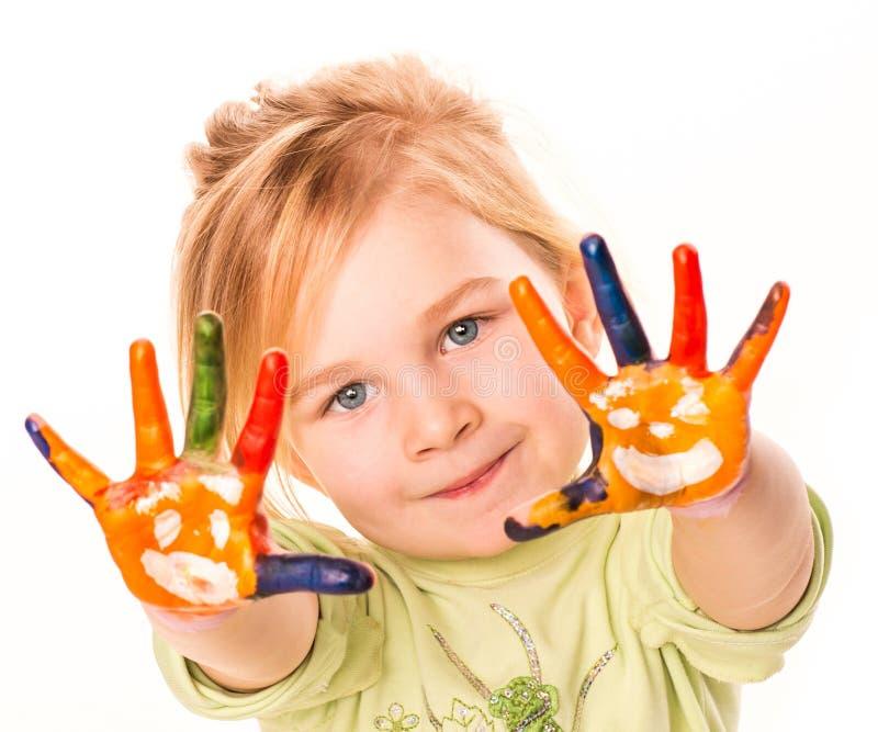Portret van een gelukkig vrolijk meisje die haar die handen tonen in heldere kleuren worden geschilderd royalty-vrije stock fotografie