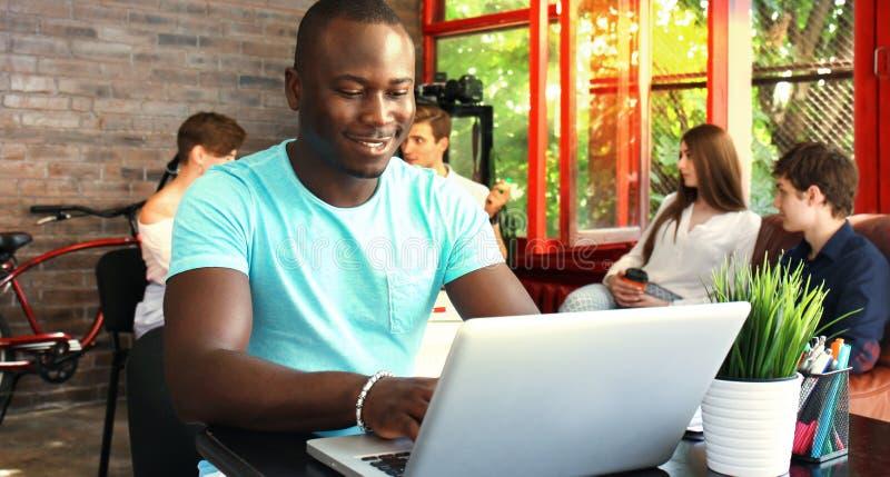 Portret van een gelukkige Afrikaanse Amerikaanse ondernemer die computer in bureau tonen royalty-vrije stock foto
