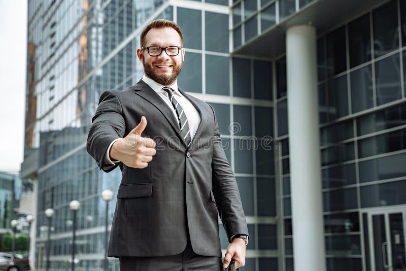 Portret van een gelukkige bedrijfsmens die zijn duim op de achtergrond van het commerciële centrum tonen stock fotografie