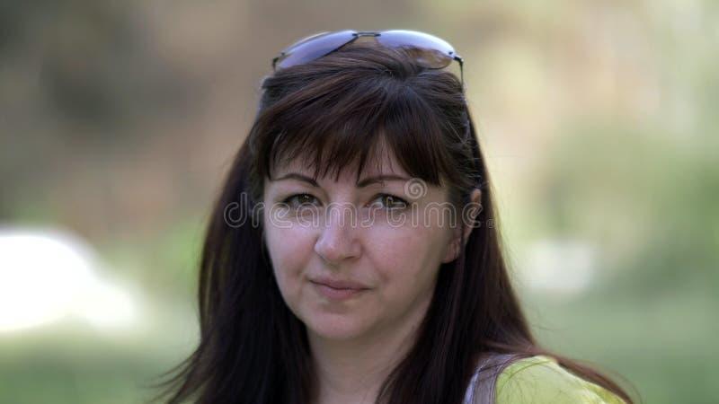 Portret van een gelukkige donkerbruine vrouw die de camera bekijken stock foto's